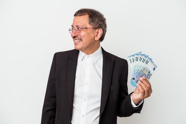 Mężczyzna w średnim wieku indyjskich przedsiębiorstw posiadających rachunki na białym tle wygląda na bok uśmiechnięty, wesoły i przyjemny.