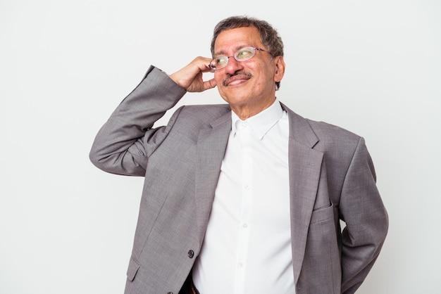 Mężczyzna w średnim wieku indyjskiego biznesu na białym tle dotykając tyłu głowy, myśląc i dokonując wyboru.