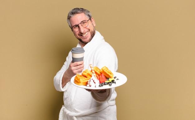Mężczyzna w średnim wieku je gofry na śniadanie?