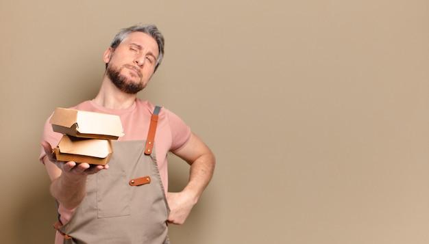 Mężczyzna w średnim wieku kucharz z hamburgerami. koncepcja grilla