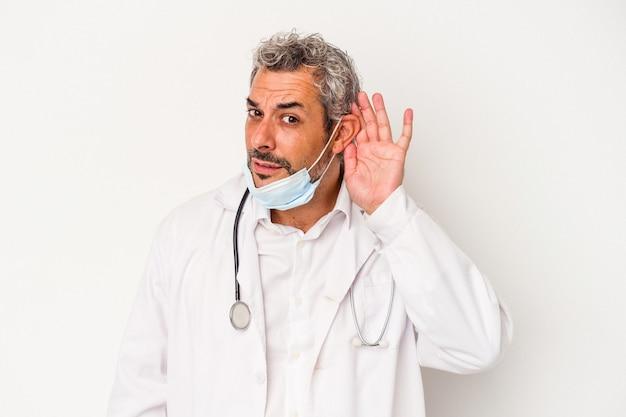 Mężczyzna w średnim wieku lekarz ubrany w maskę na wirusa na białym tle próbuje słuchać plotek.