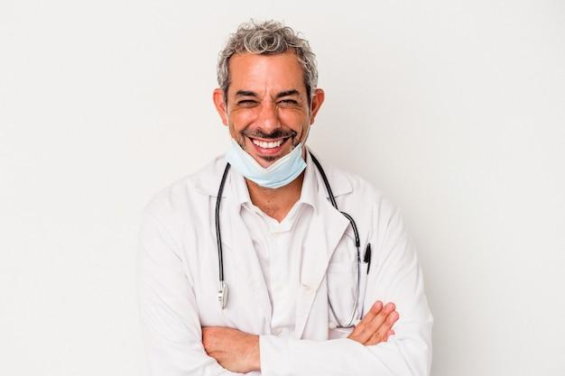 Mężczyzna w średnim wieku, lekarz, ubrany w maskę na wirusa na białym tle, śmiejąc się i bawiąc.
