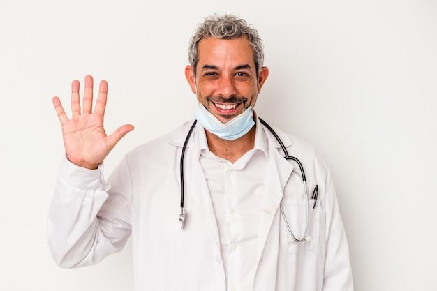 Mężczyzna w średnim wieku, lekarz, ubrany w maskę na wirusa na białym tle, uśmiechnięty wesoły, pokazując numer pięć palcami.