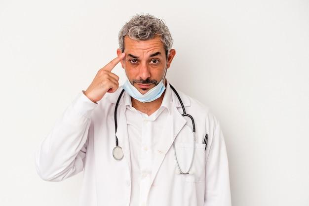 Mężczyzna w średnim wieku, lekarz, ubrany w maskę na wirusa na białym tle, wskazując świątynię palcem, myśląc, koncentrując się na zadaniu.