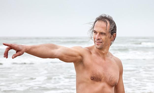 Mężczyzna w średnim wieku lubi przyrodę nad morzem i wskazuje na coś w oddali