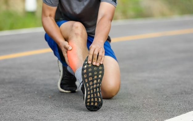 Mężczyzna w średnim wieku ma skurcze podczas joggingu. zatrzymaj i wmasuj łydkę