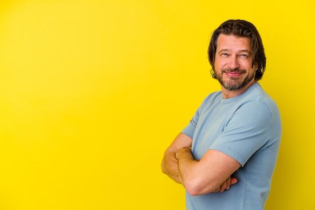 Mężczyzna w średnim wieku na białym tle na żółtej ścianie uśmiechnięty pewnie ze skrzyżowanymi rękami