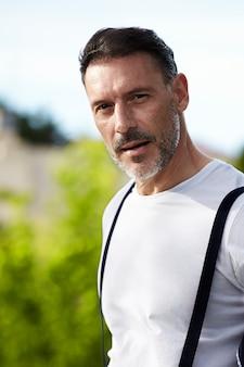 Mężczyzna w średnim wieku na sobie białą koszulę z szelkami