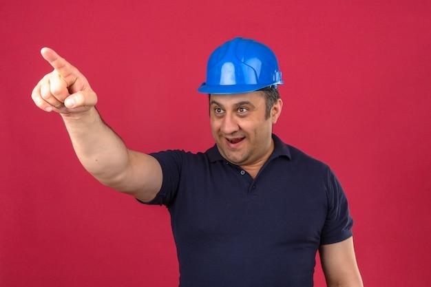 Mężczyzna w średnim wieku na sobie koszulkę polo i hełm ochronny, wskazując na bok z radosną buźką i uśmiechając się na odosobnionej różowej ścianie