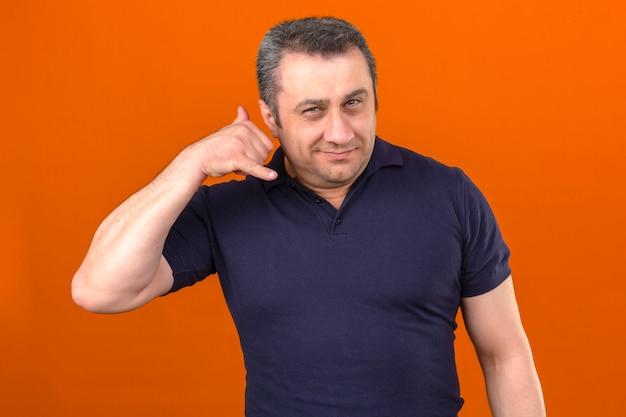 Mężczyzna w średnim wieku na sobie koszulkę polo uśmiechnięty, robi cal mnie gest palcami i uśmiecha się na pojedyncze pomarańczowe ściany