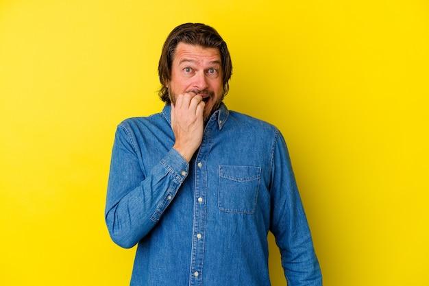 Mężczyzna w średnim wieku na żółtej ścianie gryzie paznokcie, zdenerwowany i bardzo niespokojny