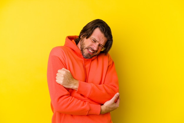 Mężczyzna w średnim wieku na żółtej ścianie masuje łokieć, cierpiący po złym ruchu