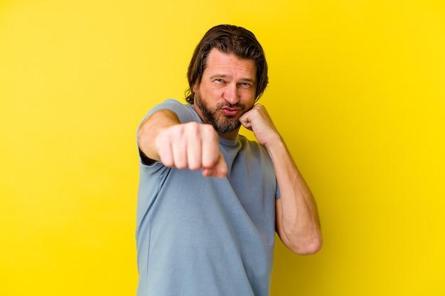 Mężczyzna w średnim wieku na żółtej ścianie rzuca cios, złość, walka z powodu kłótni, boks