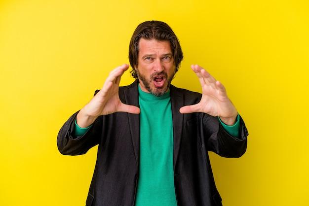 Mężczyzna w średnim wieku na żółtej ścianie trzyma coś z palmami, oferując z przodu