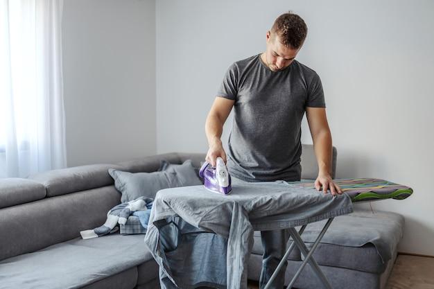 Mężczyzna w średnim wieku niezadowolony z konieczności prasowania ubrań
