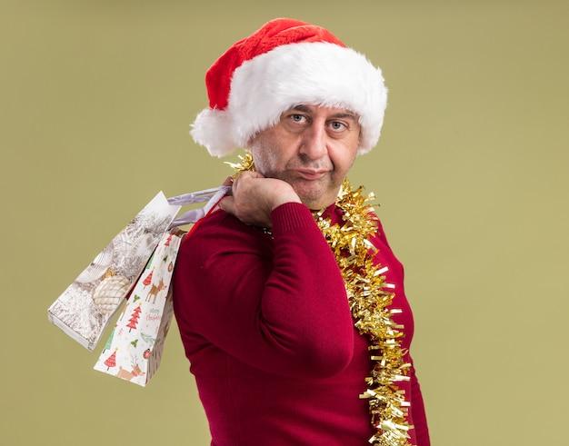 Mężczyzna w średnim wieku noszący świąteczny kapelusz mikołaja z blichtrem na szyi trzymający papierowe torby z prezentami świątecznymi z pewnym siebie wyrazem twarzy stojący nad zieloną ścianą