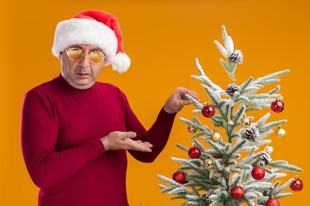 Mężczyzna w średnim wieku noszący świąteczny kapelusz mikołajowy w ciemnoczerwony golf i żółte okulary dekorujący choinkę prezentującą rękę stojącą nad pomarańczową ścianą