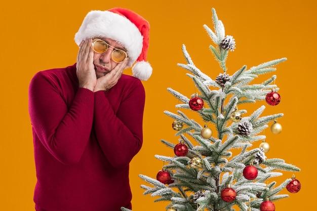 Mężczyzna w średnim wieku noszący świąteczny kapelusz mikołajowy w ciemnoczerwonym golfie i żółtych okularach martwi się stojąc obok choinki nad pomarańczową ścianą