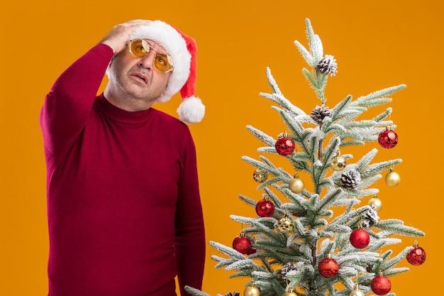 Mężczyzna w średnim wieku noszący świąteczny kapelusz mikołajowy w ciemnoczerwonym golfie i żółtych okularach patrzący w górę zdziwiony stojący obok choinki nad pomarańczową ścianą