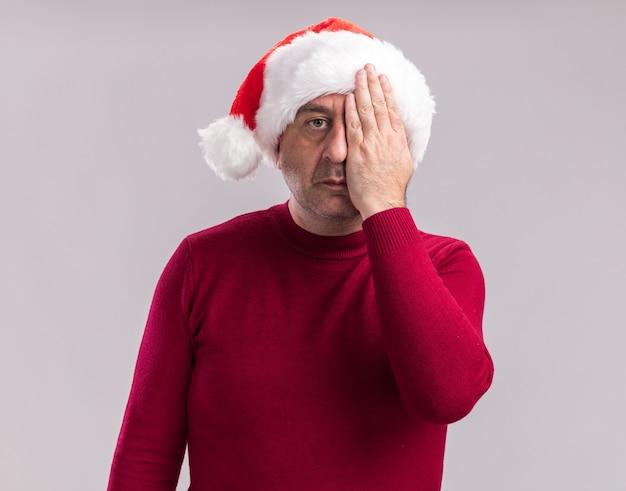 Mężczyzna w średnim wieku noszący świąteczny kapelusz mikołajowy z poważną twarzą zakrywającą jedno ty ręką stojącą nad białą ścianą