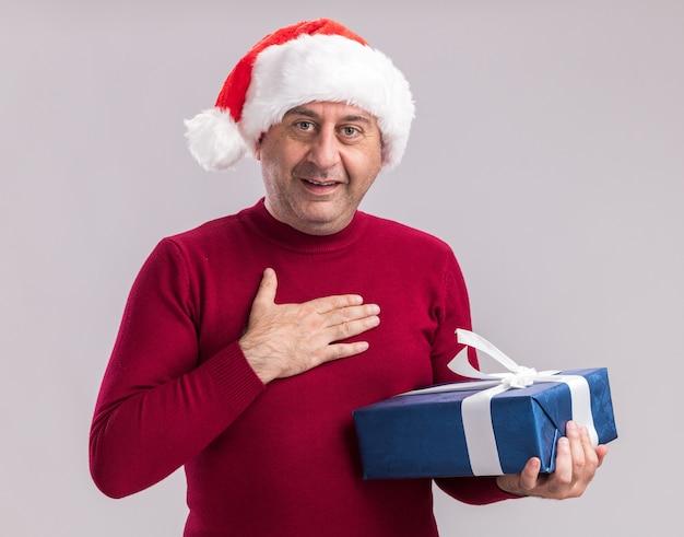 Mężczyzna w średnim wieku noszący świąteczny santa hat trzymający świąteczny prezent z uśmiechniętą twarzą stojącą nad białą ścianą