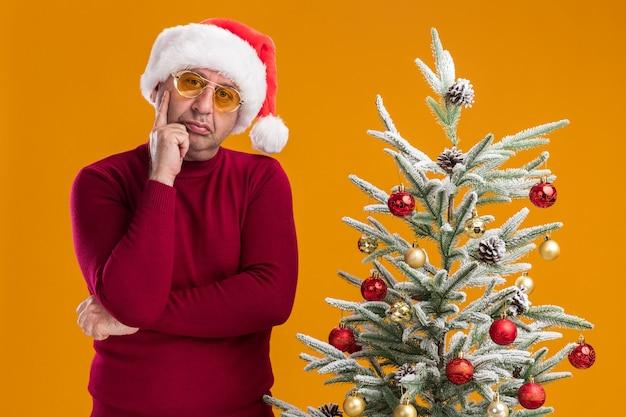 Mężczyzna w średnim wieku noszący świąteczny santa hat w ciemnoczerwonym golfie i żółtych okularach zdziwiony stojąc obok choinki nad pomarańczową ścianą