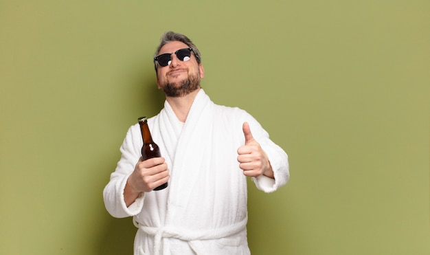 Mężczyzna w średnim wieku noszący szlafrok i pijący piwo
