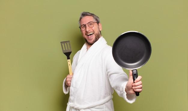 Mężczyzna w średnim wieku noszący szlafrok i uczący się gotować na patelni