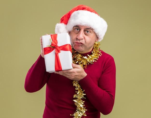 Mężczyzna w średnim wieku noszenie christmas santa hat z blichtr na szyi trzyma prezent gwiazdkowy patrząc na kamery z niejasnym wyrazem stojącym na zielonym tle
