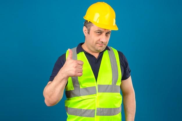 Mężczyzna w średnim wieku noszenie żółtej kamizelki i hełmu ochronnego, uśmiechając się i pokazując kciuki do góry na odosobnionej niebieskiej ścianie