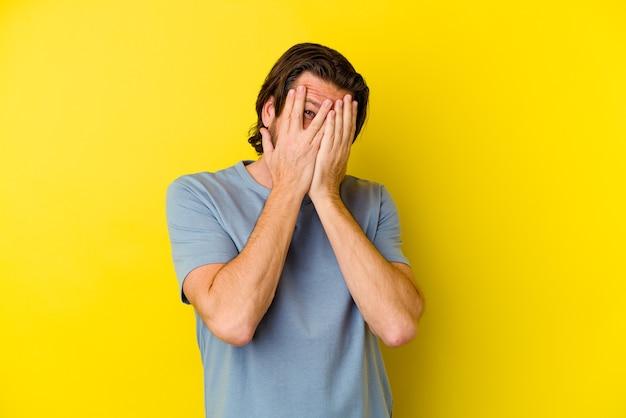Mężczyzna w średnim wieku, odizolowany na żółtej ścianie, mruga przez palce przestraszony i zdenerwowany