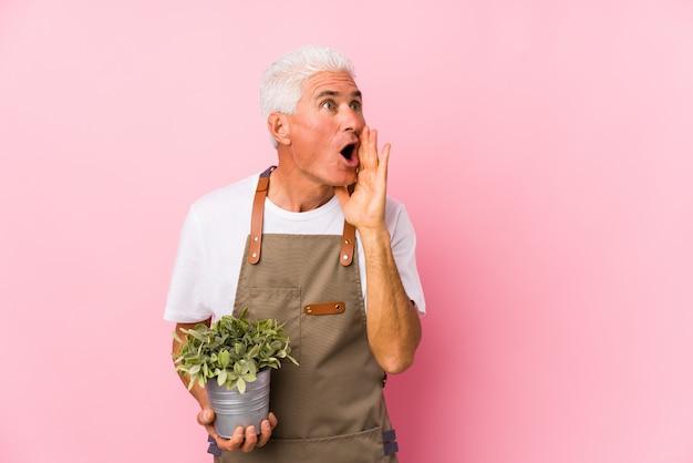 Mężczyzna w średnim wieku ogrodnik odizolowany mówi tajemniczą wiadomość o hamowaniu na gorąco i odwraca wzrok