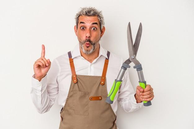 Mężczyzna w średnim wieku ogrodnik trzyma nożyczki na białym tle o jakiś świetny pomysł, pojęcie kreatywności.