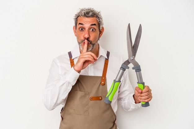 Mężczyzna w średnim wieku ogrodnik trzymający nożyczki na białym tle dochowując tajemnicy lub prosząc o ciszę.