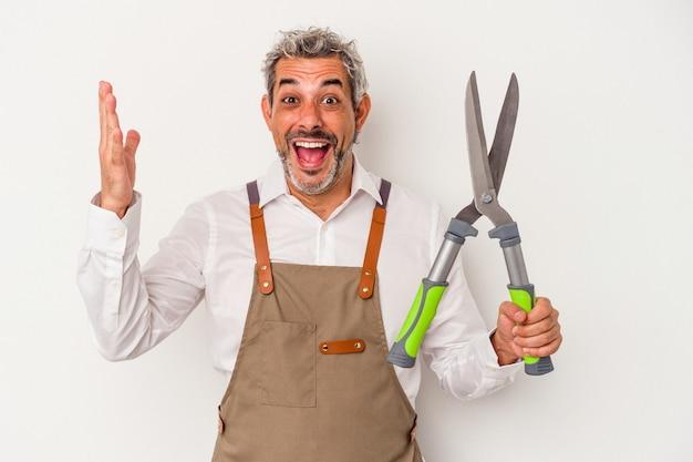 Mężczyzna w średnim wieku ogrodnik trzymający nożyczki na białym tle otrzymujący miłą niespodziankę, podekscytowany i podnoszący ręce.
