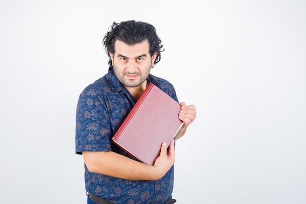 Mężczyzna w średnim wieku patrząc na kamery, trzymając książkę w koszuli i patrząc pewnie. przedni widok.