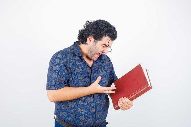 Mężczyzna w średnim wieku patrząc na książkę w koszuli i patrząc wściekły. przedni widok.