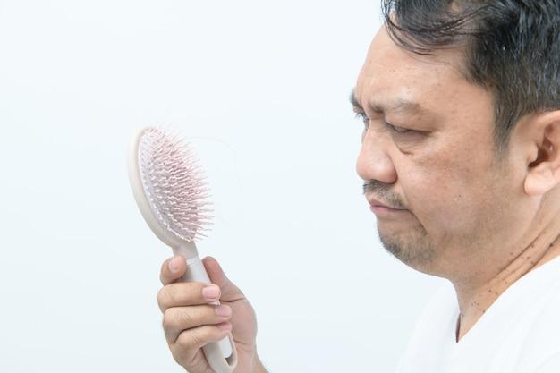 Mężczyzna w średnim wieku patrząc na szczotkę grzebieniową z wypadającymi włosami i zestresowany problemami z wypadaniem włosów