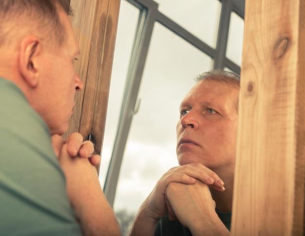 Mężczyzna w średnim wieku, patrząc poważnie w lustrzane odbicie, myśląc o swoim wieku i życiu.