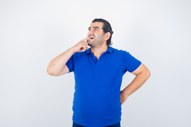 Mężczyzna w średnim wieku, patrząc w górę podczas gryzienia palca w niebieską koszulkę i patrząc zamyślony, widok z przodu.