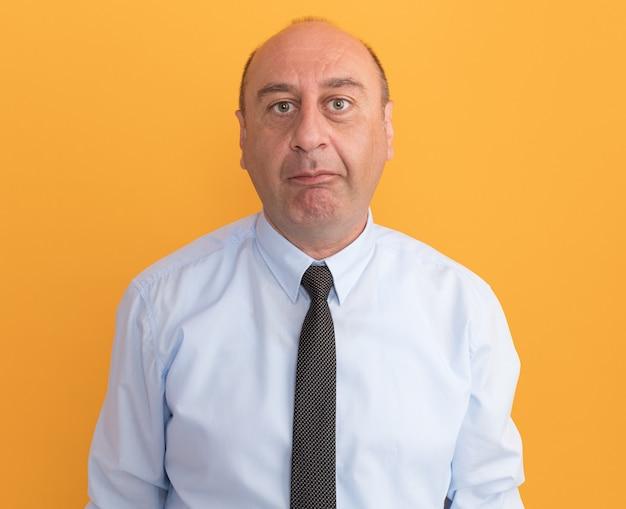 Mężczyzna w średnim wieku patrząc z przodu na sobie białą koszulkę z krawatem na białym tle na pomarańczowej ścianie