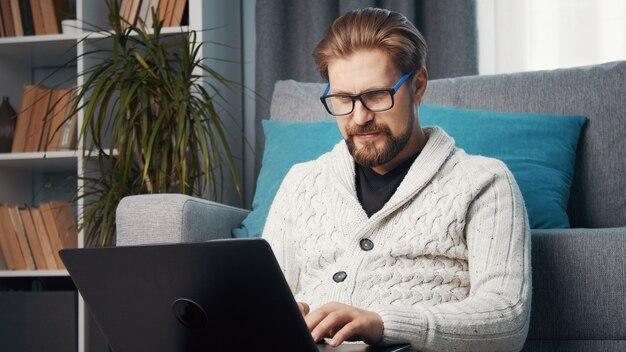 Mężczyzna w średnim wieku, pracujący w domu, siedzący na podłodze oparty o kanapę za pomocą laptopa, kwarantanna