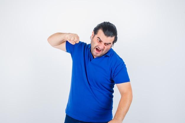 Mężczyzna w średnim wieku przygotowuje się do uderzenia w koszulkę polo i wygląda zirytowany, widok z przodu.