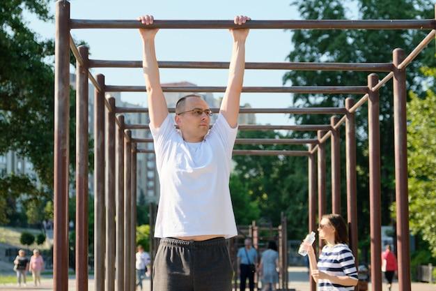Mężczyzna w średnim wieku robi pull up ćwiczenia na poziomym pasku odkryty