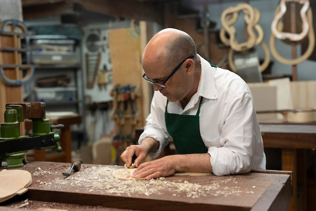Mężczyzna w średnim wieku sam wytwarza instrumenty w swoim warsztacie