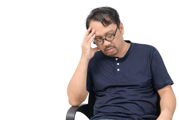 Mężczyzna w średnim wieku siedzi na krześle i czuje się zestresowany i ból głowy na białym tle. pojęcie problemu i opieki zdrowotnej.