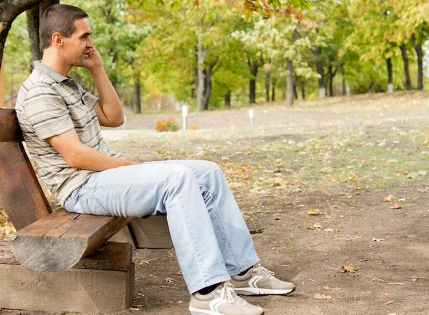 Mężczyzna w średnim wieku siedzi na rustykalnej drewnianej ławce w parku i rozmawia przez telefon komórkowy