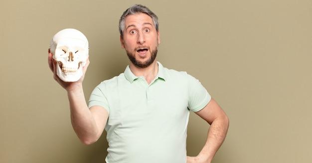 Mężczyzna w średnim wieku trzyma ludzką czaszkę