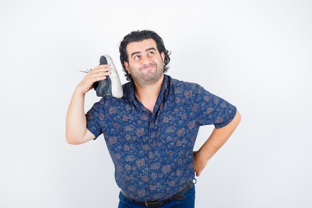 Mężczyzna w średnim wieku, trzymając but na ramieniu w koszuli i patrząc zamyślony, widok z przodu.