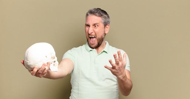 Mężczyzna w średnim wieku trzymający ludzką czaszkę